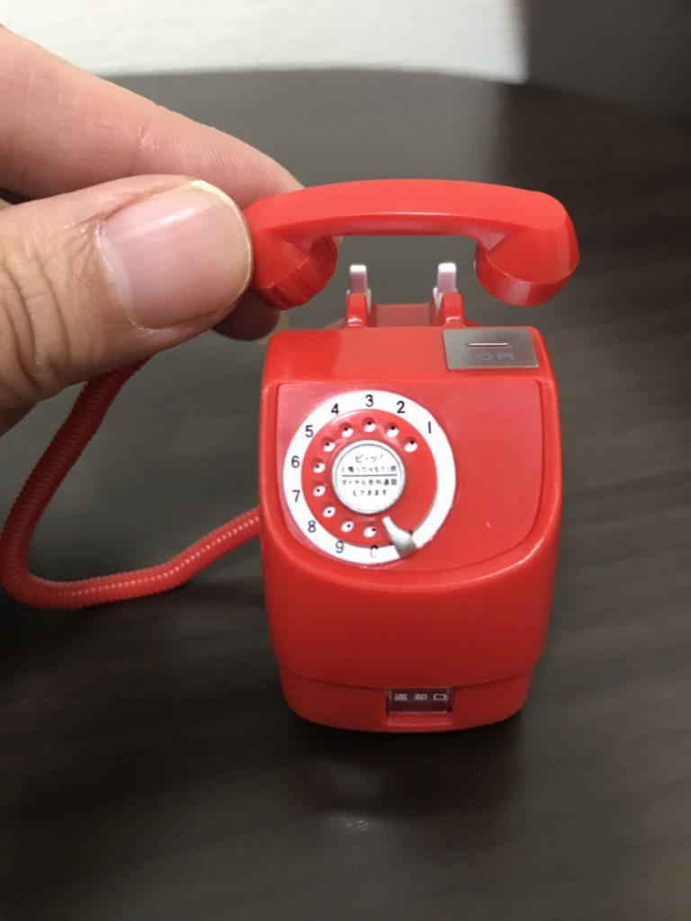 NTT東日本 公衆電話ガチャコレクションの新型赤電話を指で持った画像