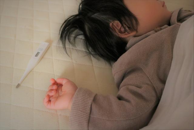 熱があるのに眠らず遊ぶ子供の体温計と子供の画像