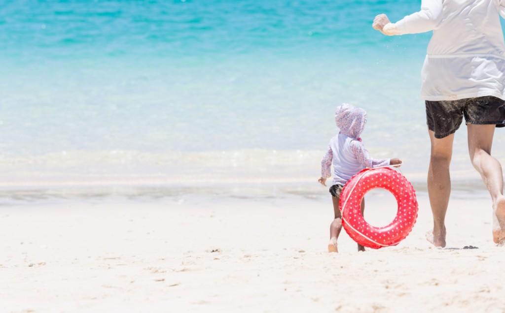 親子が仲良く海辺を走る画像